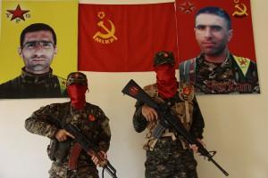 Kämpfer der MLKP vor den Bildern zweier Märtyrer