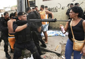 A police officer aims a machine gun at a woman as people protest beside a body killed during a shootout involving police and suspected drug traffickers at the Complexo de Alemao slum in Rio de Janeiro, Tuesday, Feb. 13, 2007. The violence comes just before the city's Carnival celebrations next Feb 18 and Feb 19. Rio is one of the most violent cities in the world with an annual homicide rate of about 50 per 100,000. (AP Photo/Ricardo Moraes)