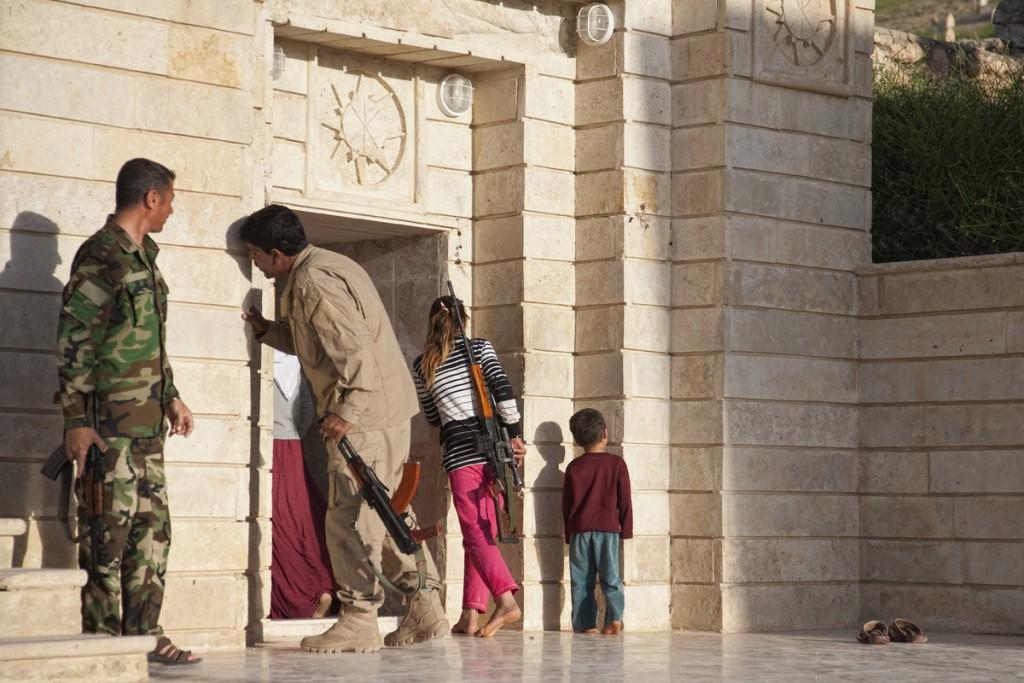 Eine jesidische Familie besucht den heiligen Tempel Sherfedin im Nord-Irak am 6. Mai, 2015. Die Tochter trägt dabei eine der Waffen des Vaters mit sich. Nur wenige Monate zuvor hatte Daesh Sherfedin umzingelt und hunderte Jesiden umgebracht oder entführt. Foto: Benjamin Hiller