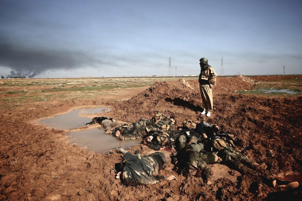 Mabast, ein Leutnant der Kurdischen Peshmerga, schaut in Richtung der umkämpften Stadt Mulla Abdullah in der Nähe von Kirkuk, am 31. Januar 2015. Die toten Körper vor Ihm sind Daesh Kämpfer welche am 30. Januar versucht hatten die kurdischen Positionen anzugreifen aber durch Luftangriffe der USA daran gehindert wurden. Foto: Osie Greenway